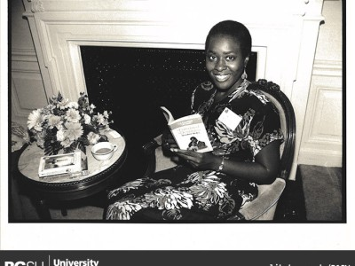 Image of Elsie B. Washington smiling at the camers while reading her 1980 novel Entwined Destinies