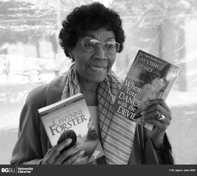 Image of author Gwynne Forster (Gwendolyn Johnson-Acsadi) holding two of her books.